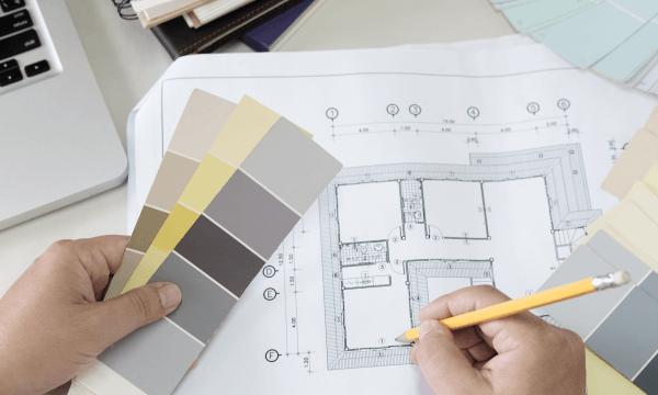pessoa-desenhando-projeto-de-reforma-com-paleta-de-cores-na-mão