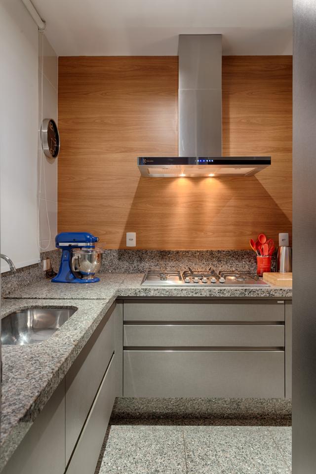 Cozinha de apartamento pequeno realizada pela equipe renata basques. Repare na utilização do espaço abaixo da bancada para armazenar os utensílios domésticos.